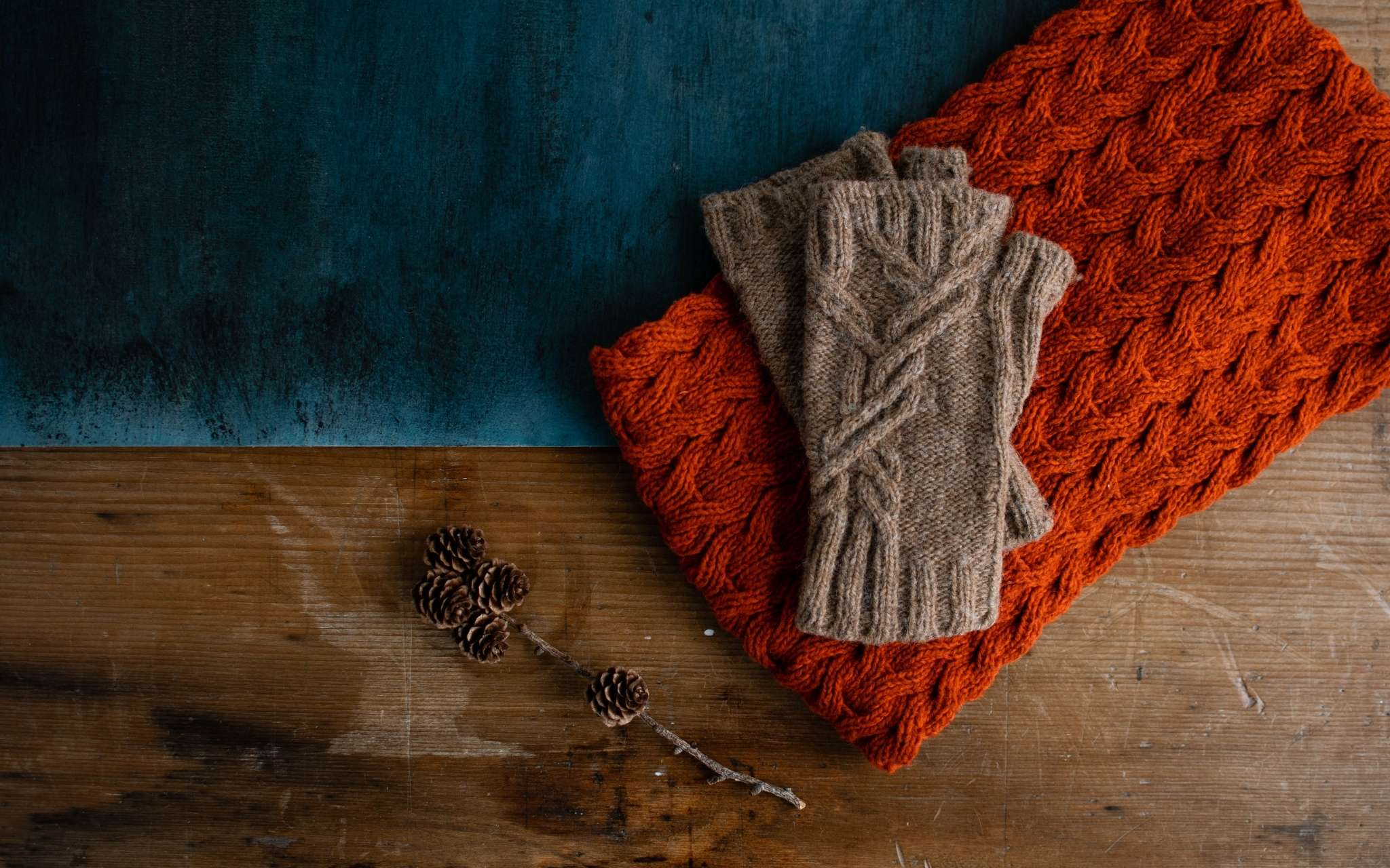 A pair of camel coloured fingerless mitts with a cable pattern lie flat on top of an orange cabled piece of fabric. They lie on a wooden surface.
