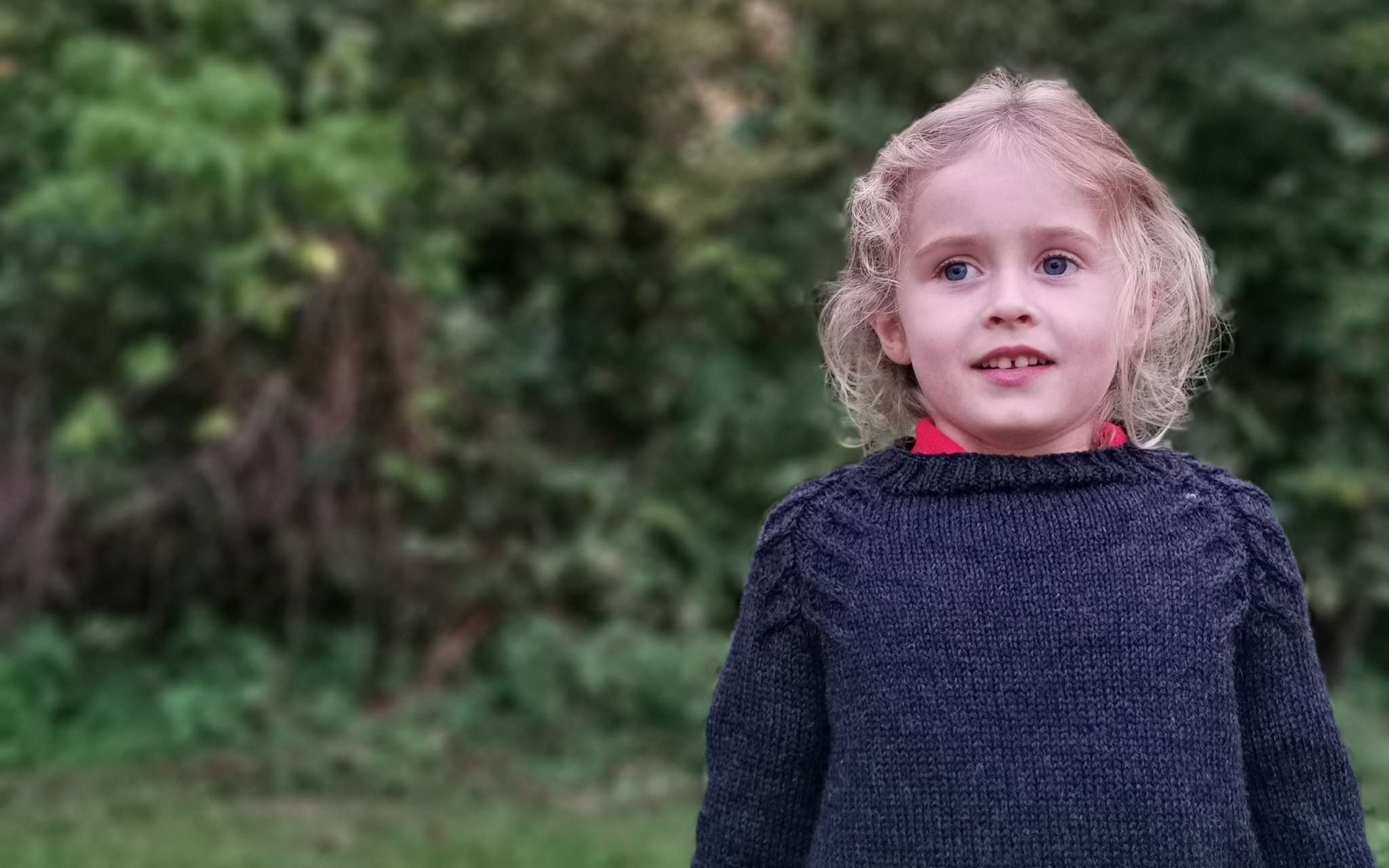 A young child with wavy blond hair wears a black sweater with cabled detailing along the raglan shaping. They are looking straight ahead and standing in a garden.