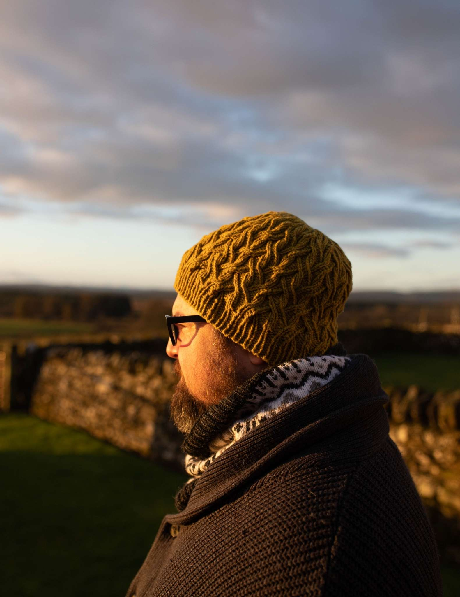 A white man with a beard and glasses looks out onto a rural landscape at sunset. He is wearing a green cabled hat and colourwork cowl