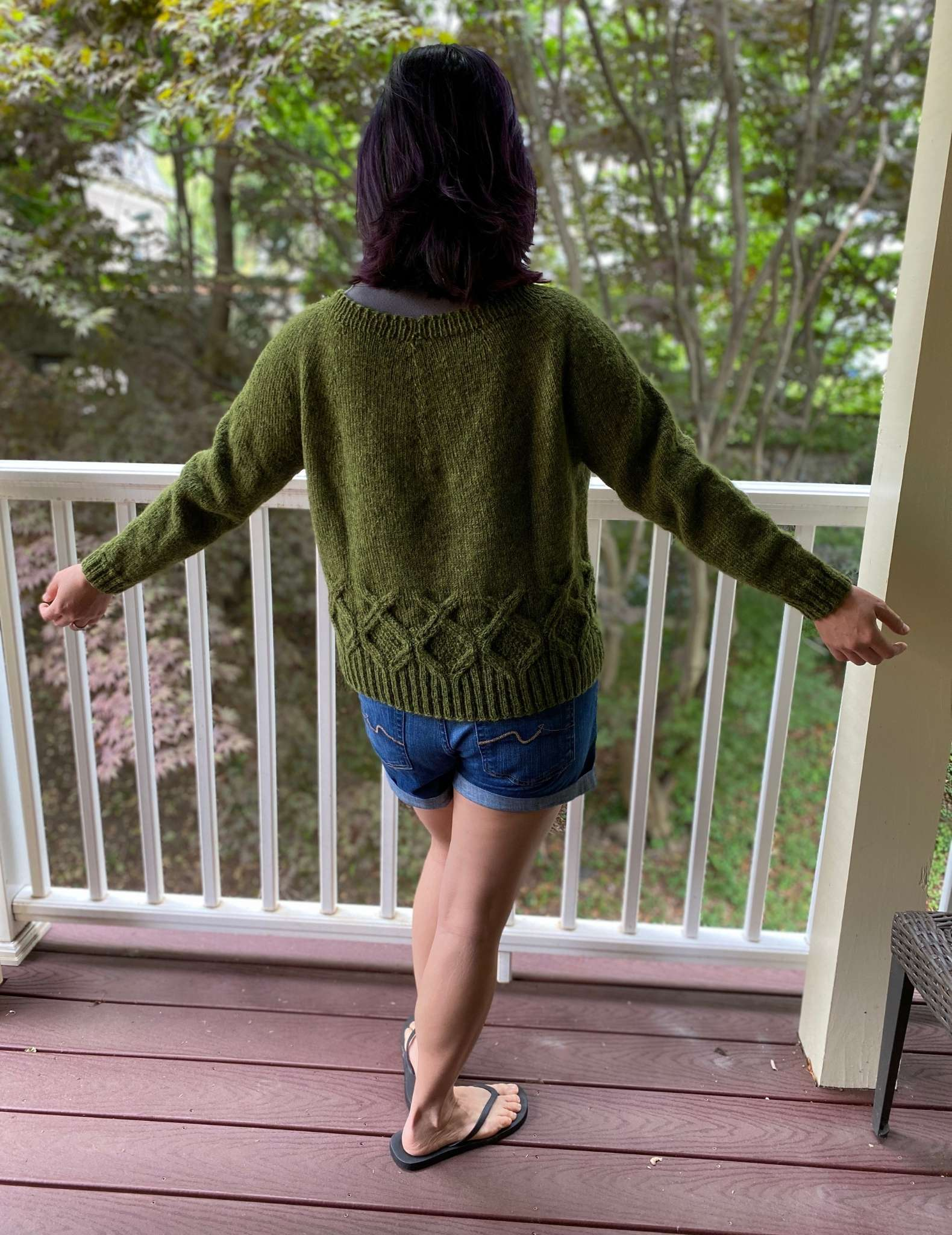 The back of an Asian female model wearing a green sweater and shorts, with arms outstretched