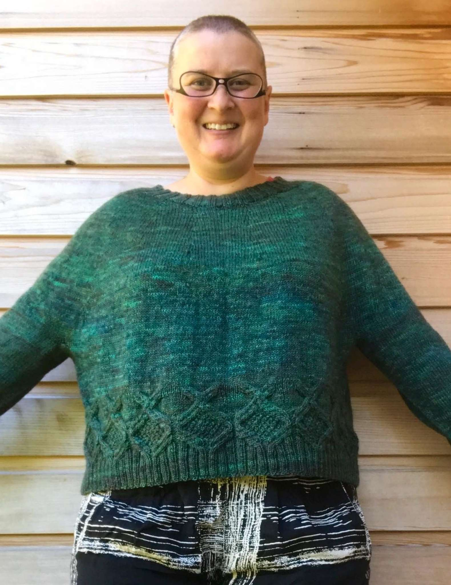 a smiling white, fat, and middle-aged model standing and wearing a green sweater with arms outstretched