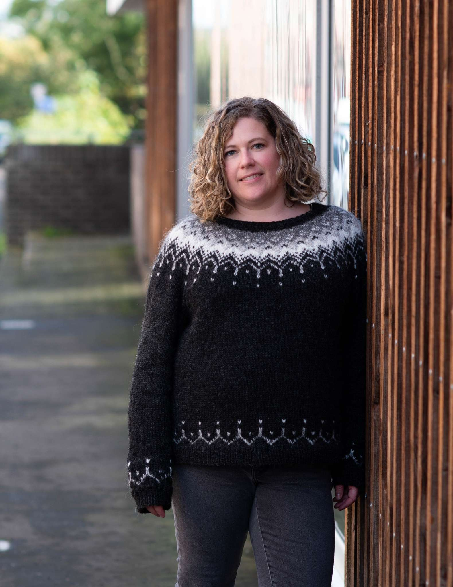 A white woman with curly hair wears a cosy black sweater with colourwork yoke in neutral colours, leaning against a wall