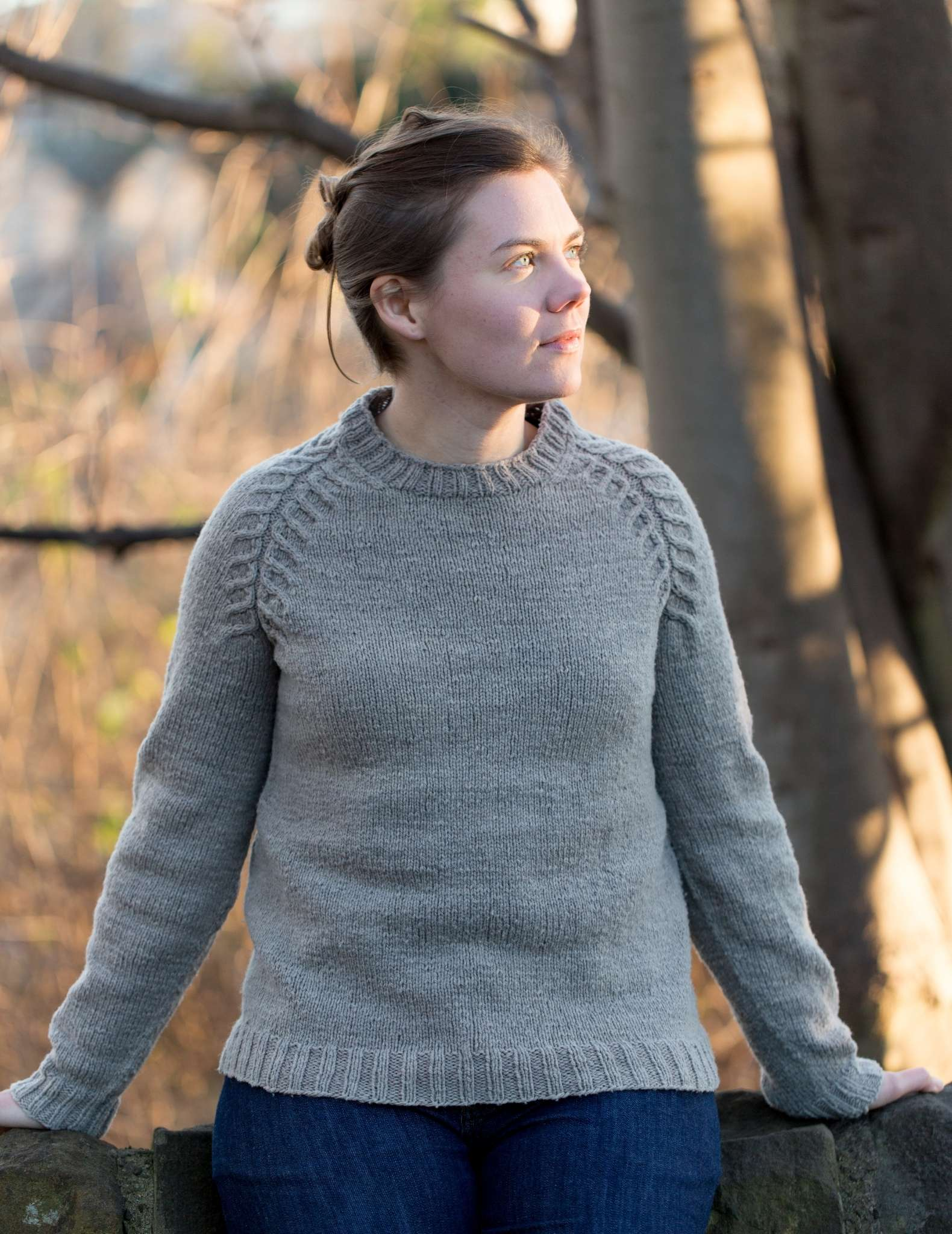 A white woman with tied back brown hair stands outdoors wearing a neutral plain sweater with cables on the shoulders.