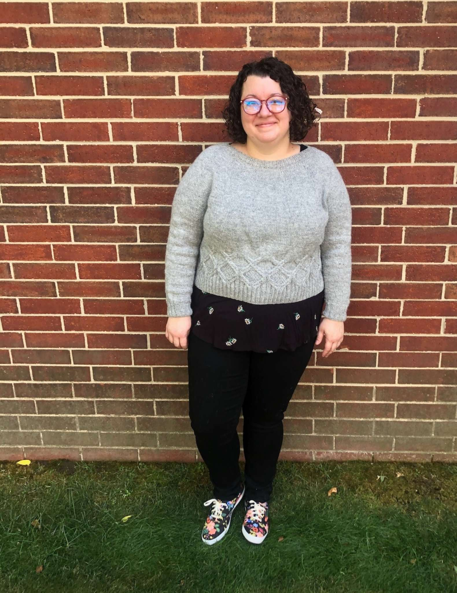 A white plus-size woman wears a natural colour cabled sweater and stands in front of a brick wall