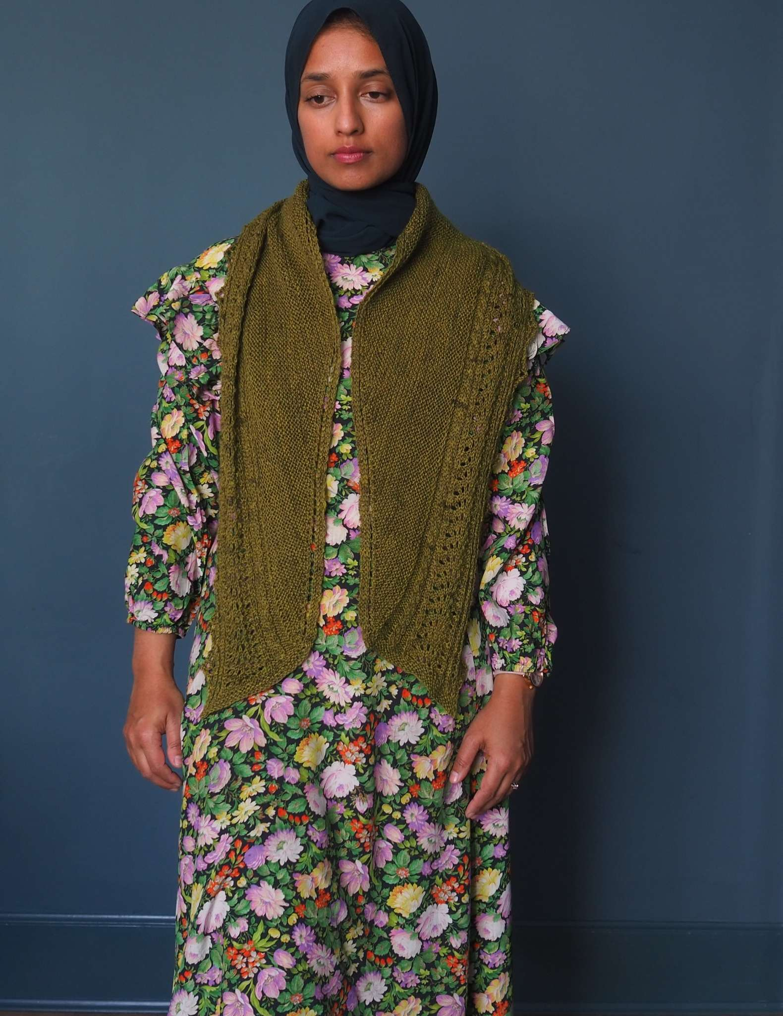 A brown woman in a hijab stands in front of a dark blue background. She is wearing a floral dress in shades of green, pink and yellow and a long green shawl is draped around her neck with the ends pointing down at the front.