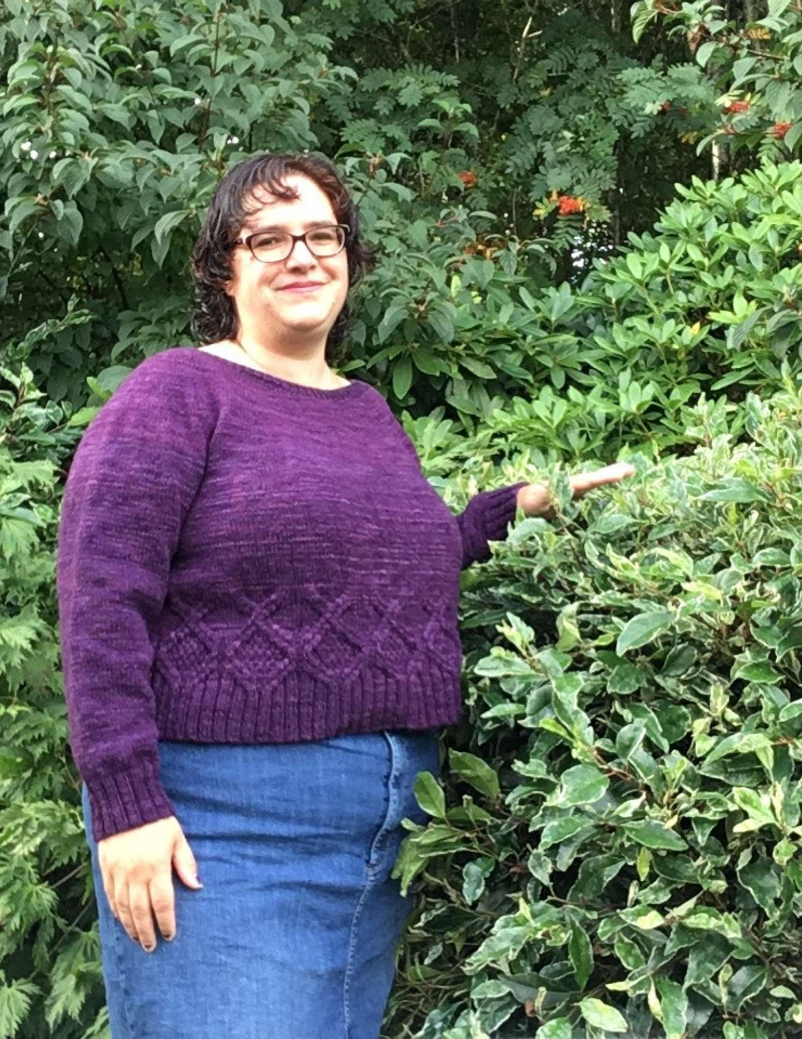 a model with dark hair wearing a purple sweater, standing in front of a bush with one arm raised
