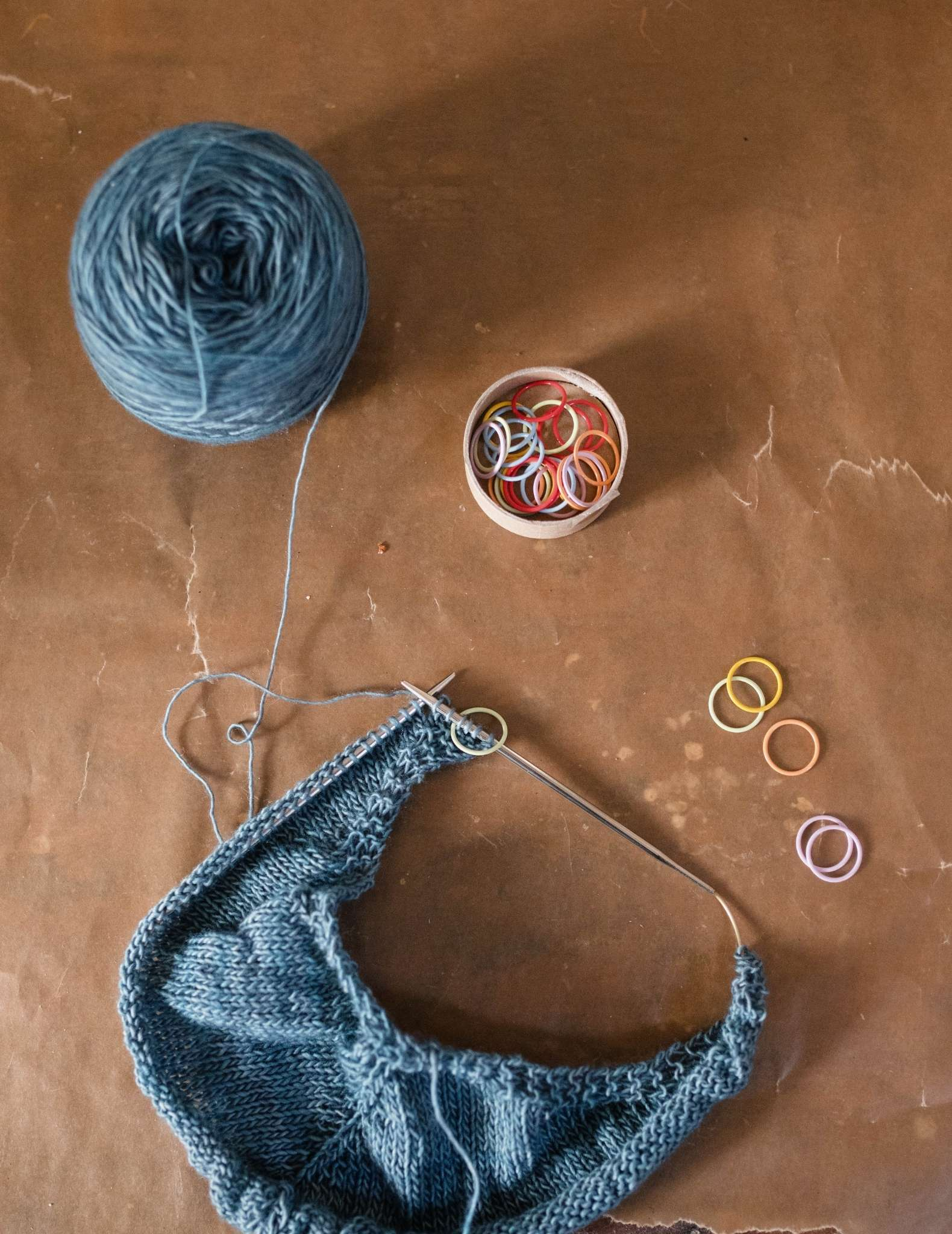 A flat lay image of a blue shawl still on the needles, a ball of attached blue yarn and pot of coloured ring stitch markers.