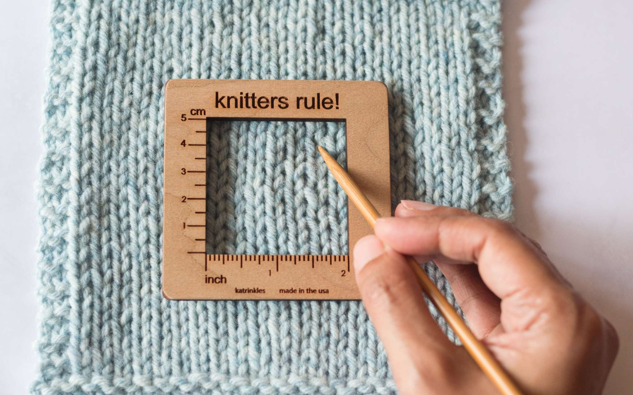 A pale blue swatch lays on a flat surface. A small square wooden measuring tools lies on top of the swatch and a wooden needle is being pointed towards the stitches in the centre.
