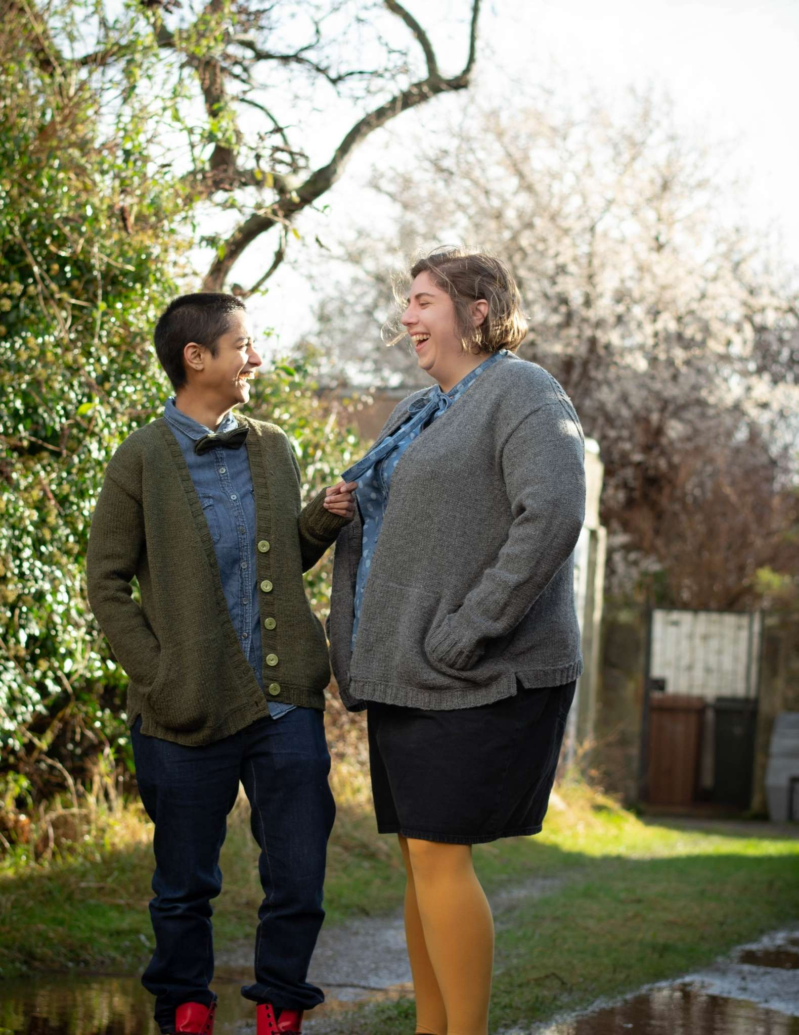 Two models wearing open, cardigans stand underneath some trees on a path through grass. They face each other and one holds the other's scarf, they are smiling at each other.
