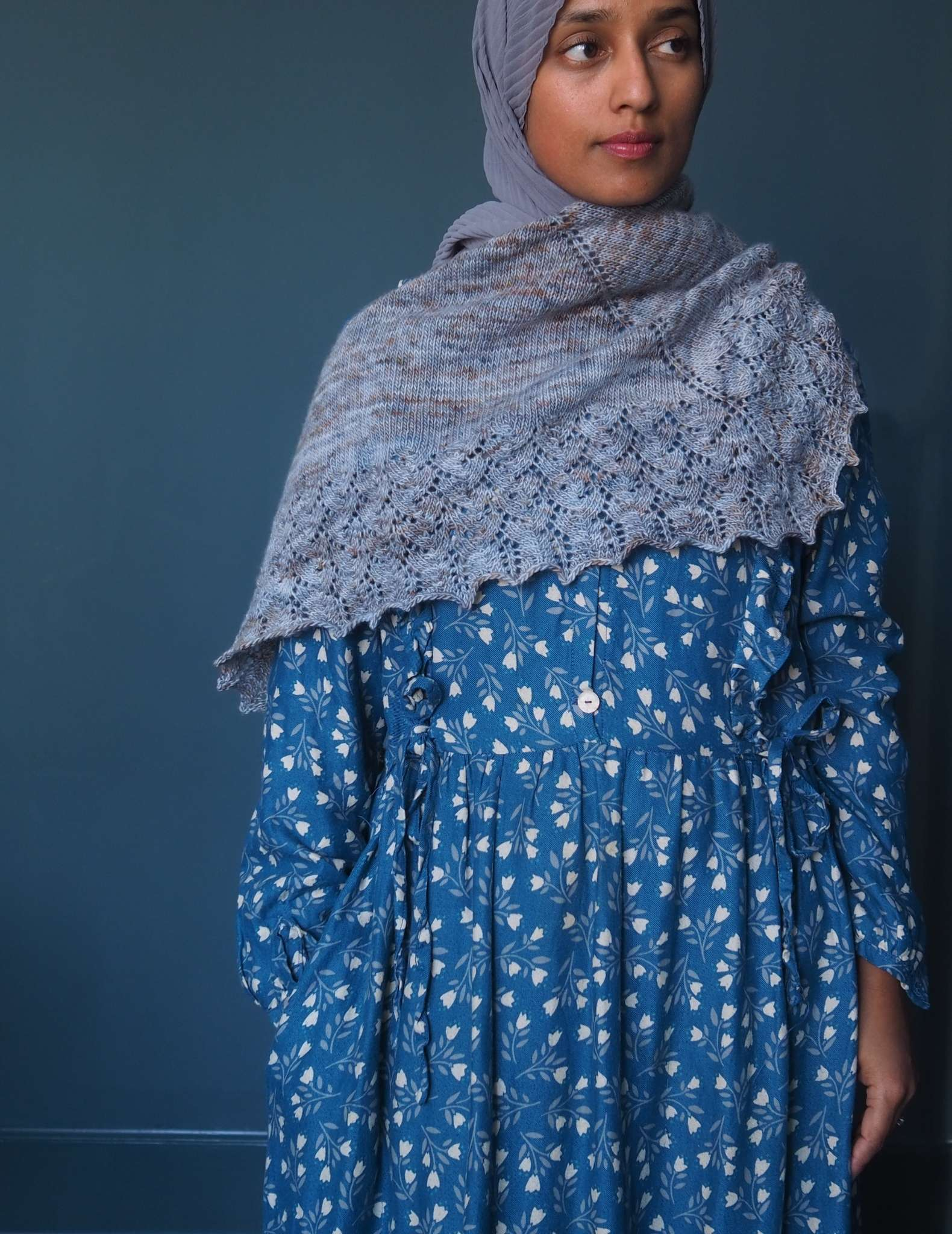 A brown woman in a hijab stands in front of a dark blue background and looks to the side. She is wearing a blue dress with small white floral print, and has a grey blue shawl wrapped around her shoulders and chest.
