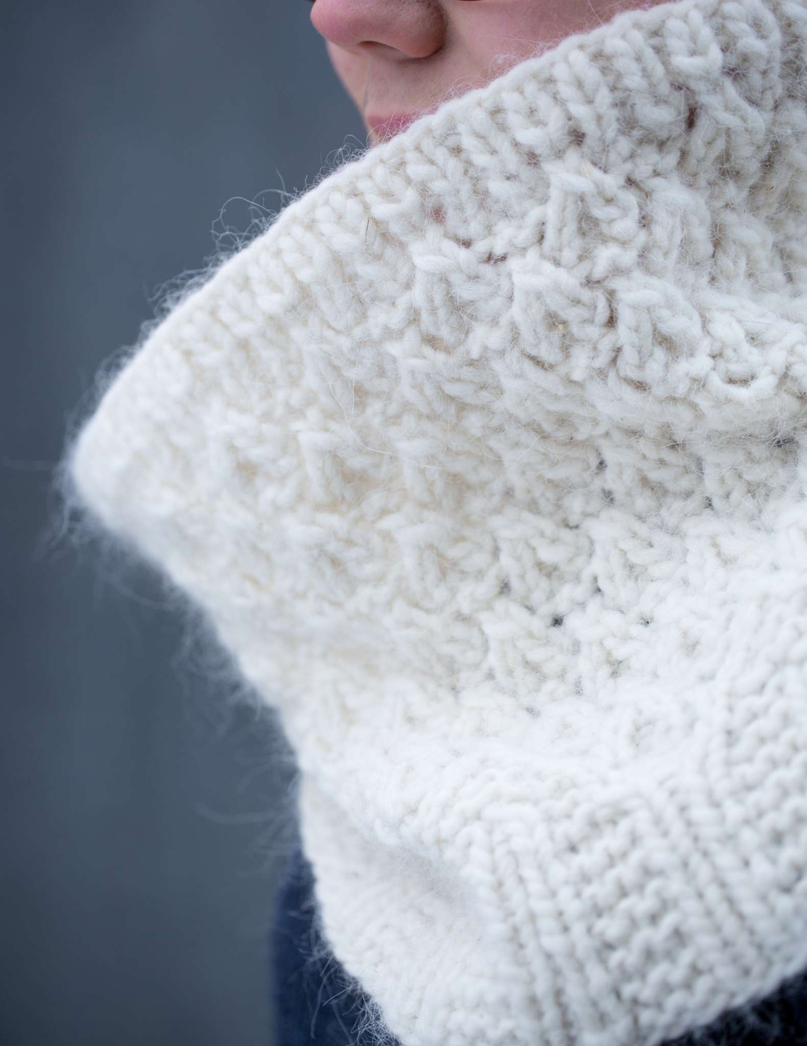 A close up of a white cowl, with only wearers nose slightly visible. The cowl is fluffy and textured.
