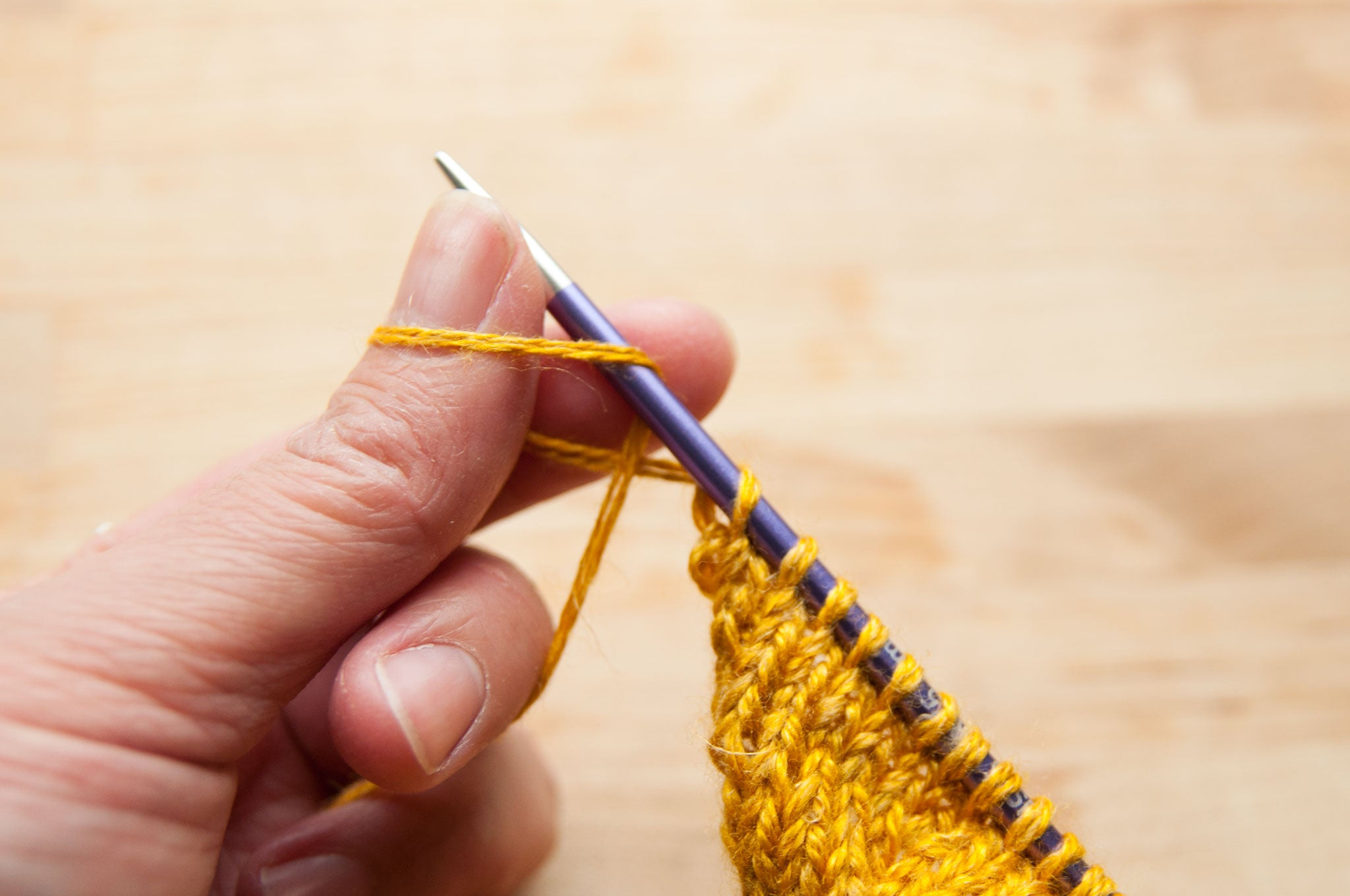 Make a twisted loop over your left thumb and place it on the needle.