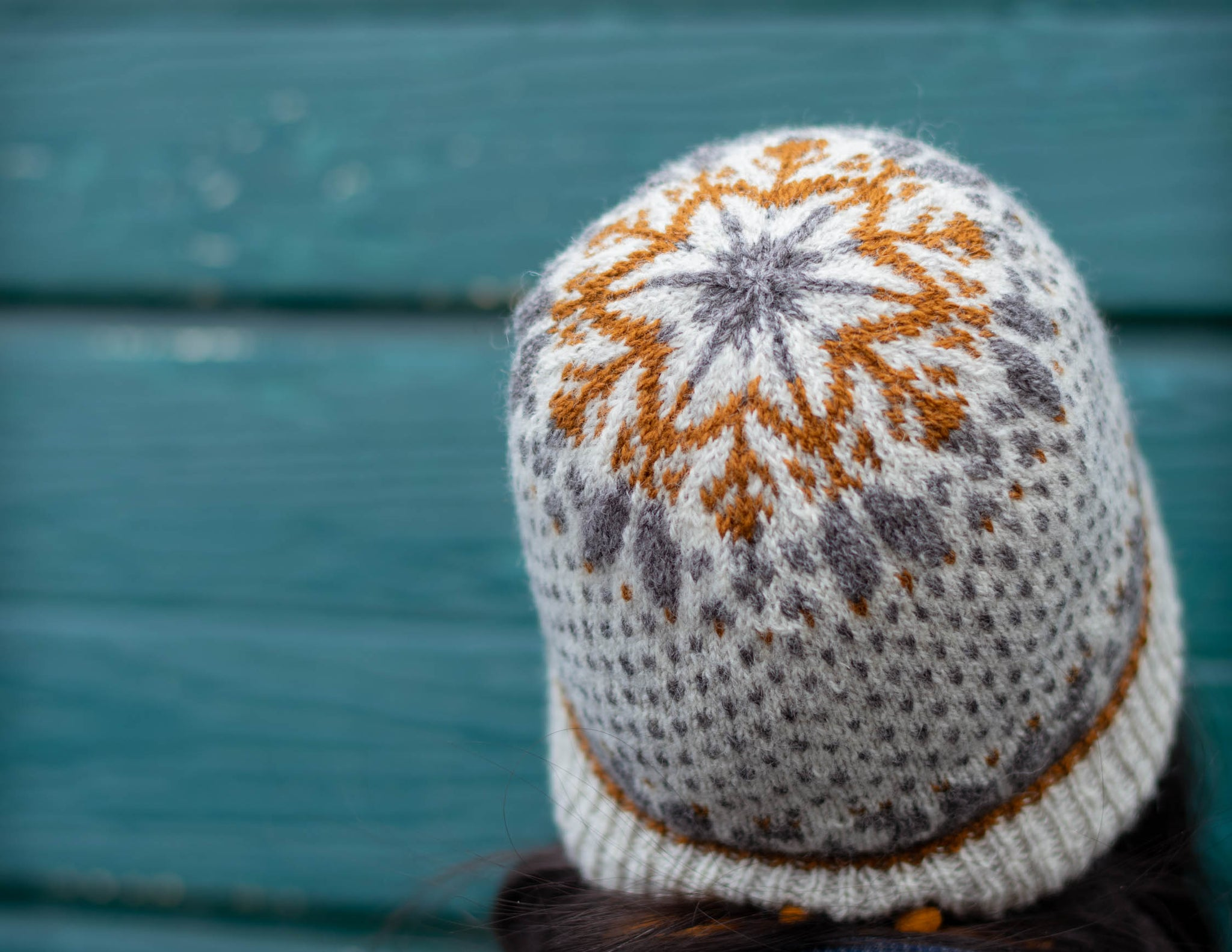 Neutral version of the Bellfield hat against a weathered teal background. The hat has a pretty snowflake design in the crown.