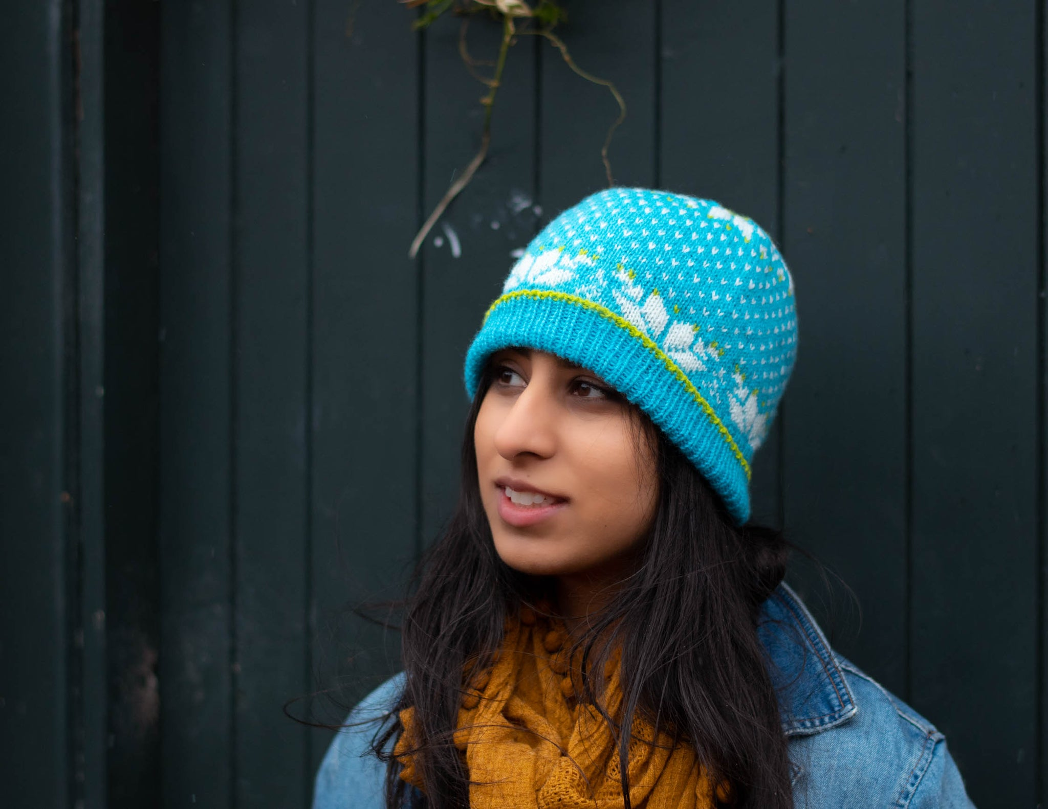 Image of a brown skinned woman with long hair, wearing a bright turquoise colourwork hat.