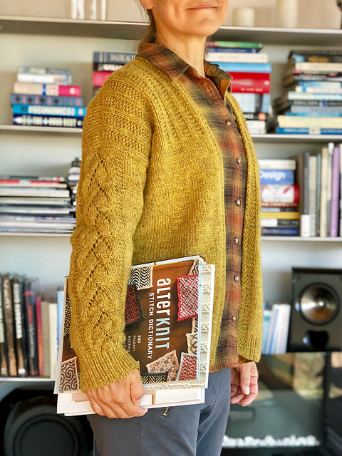 Image of a woman wearing a yellow cardigan withj lace detail on the arm and a rib pattern on the shoulders. She is in front of a bookcase and holding the Alterknits stitch dictionary.