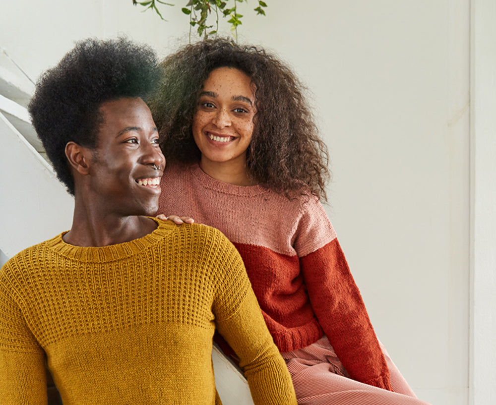 Image of a black skinned man in a close fitting yellow jumper with a textured yoke detail. He is standing in front of a lighter skinned woman with freckles wearing a colour blocked jumper in pink and red.