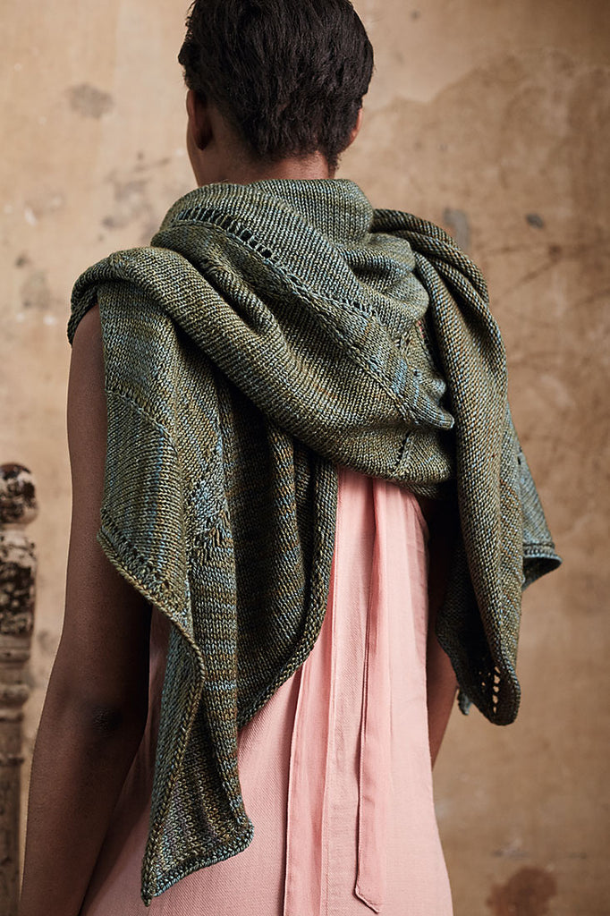 Image of a black woman with her back to the camera, wearing a large, drapey, green shawl.