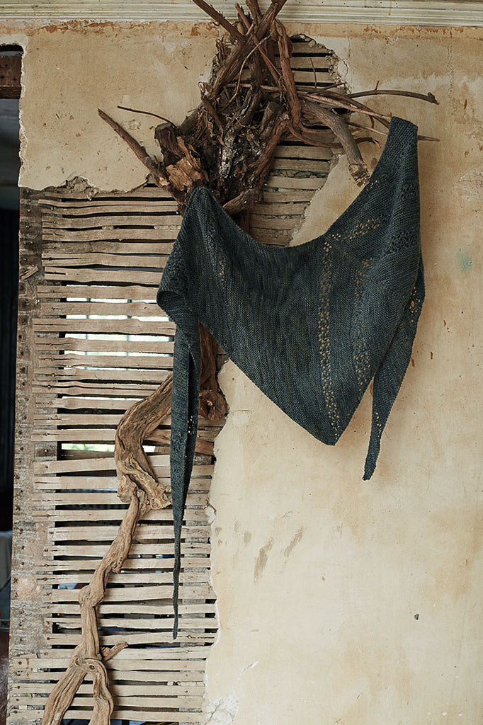 An asymmetric triangular shawl displayed against a distressed wall.
