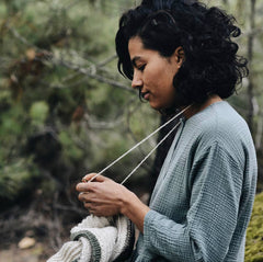 Image of a light brown skinned woman knitting with her working yarn wrapped over her neck