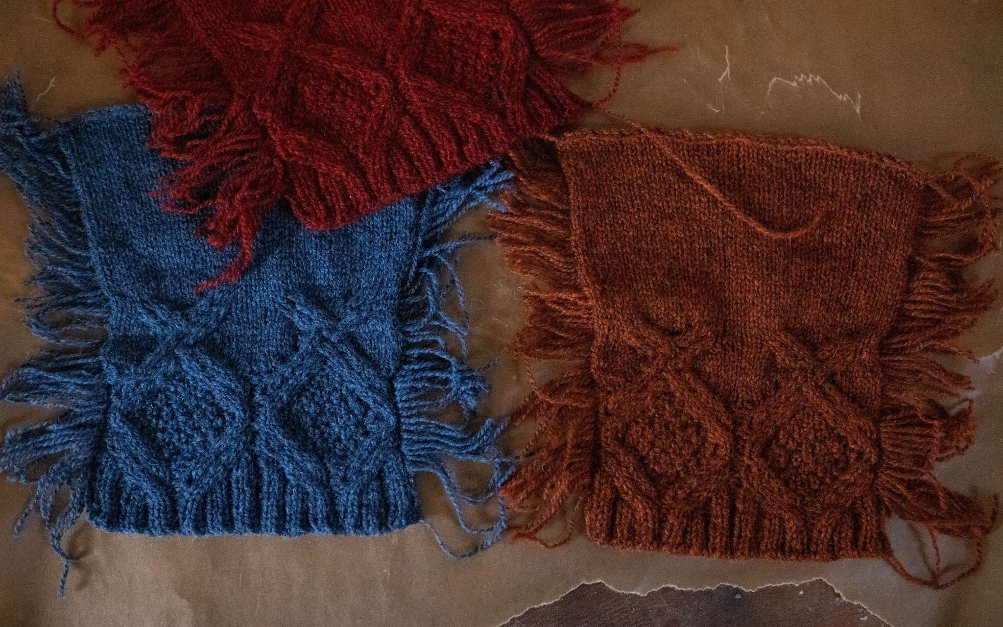 Blue and orange cabled swatches lie next to each other on a flat surface, with a red cabled swatch overlapping slightly at the top.