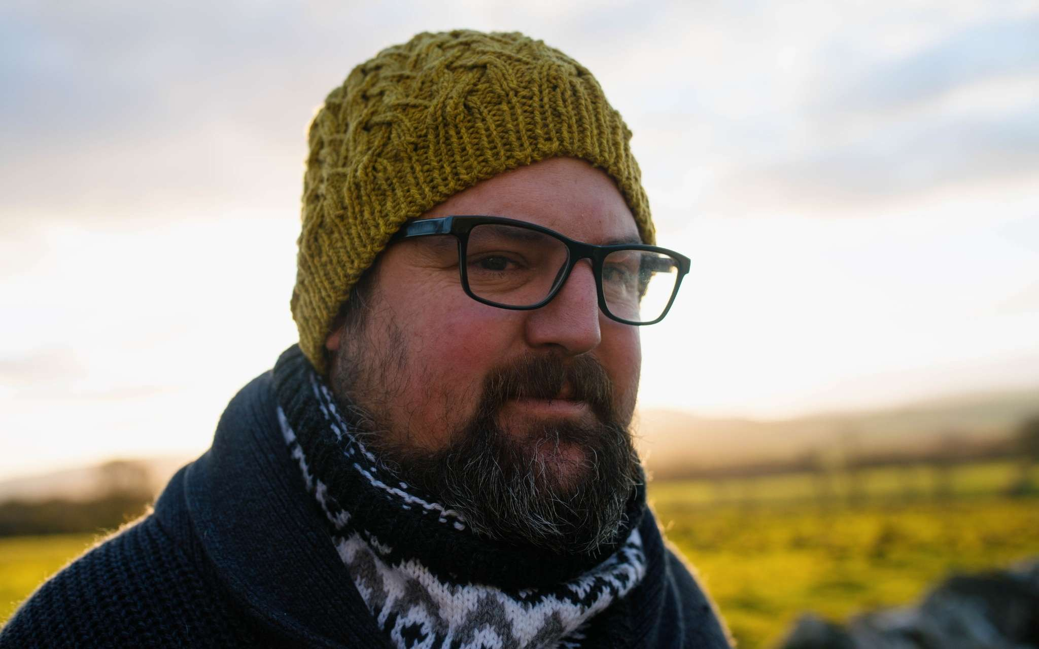 A white man with a beard and glasses stands in a rural landscape, looking to the right. He is wearing a green cabled beanie hat and colourwork cowl.