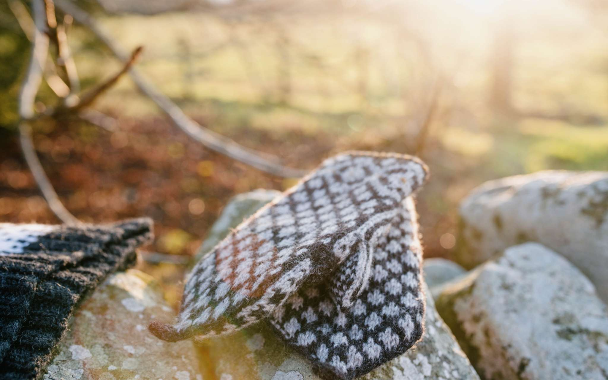 A pair of dark and cream colourwork mittens lay on top of each other, on a stone wall. The light shines in the background through a fence.