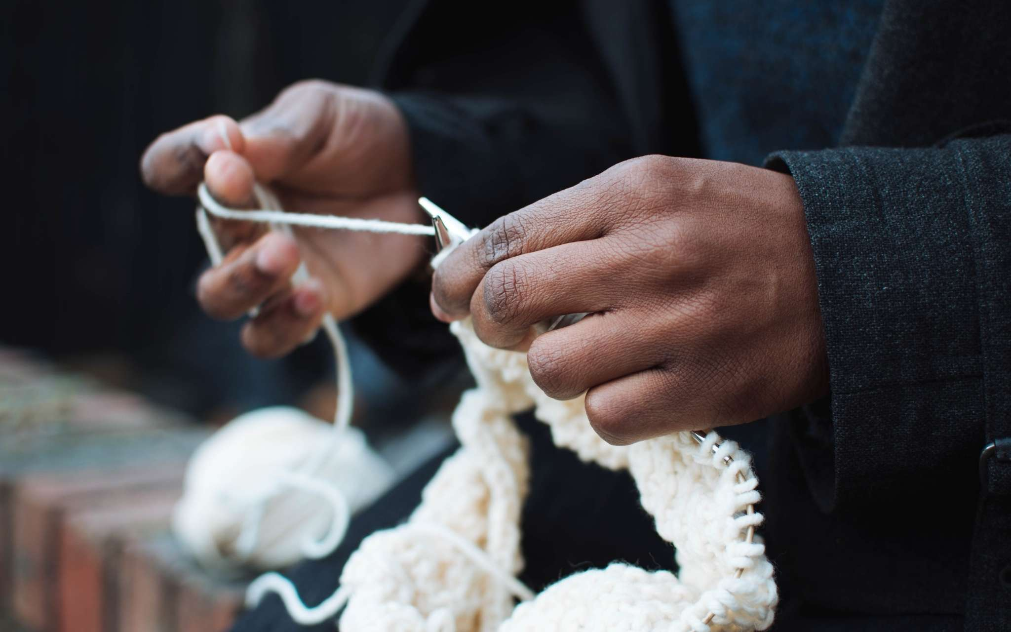 A black person knits on a white sweater with circular needs, the ball of yarn lies on a wall to the side.