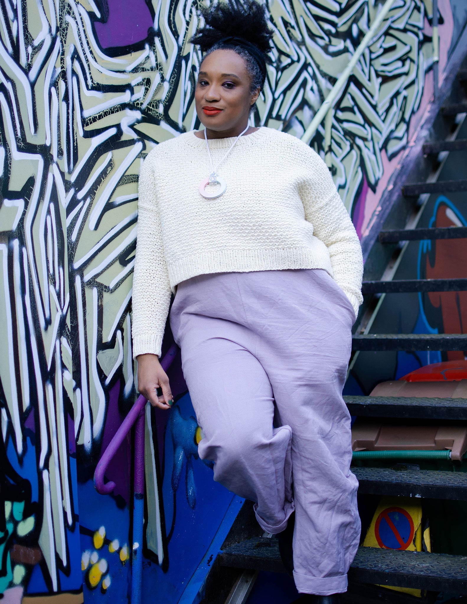 A black woman with her hair pulled up on top of her head leans against a graffitied wall. She's wearing a lavender jumpsuit with a white cropped sweater.