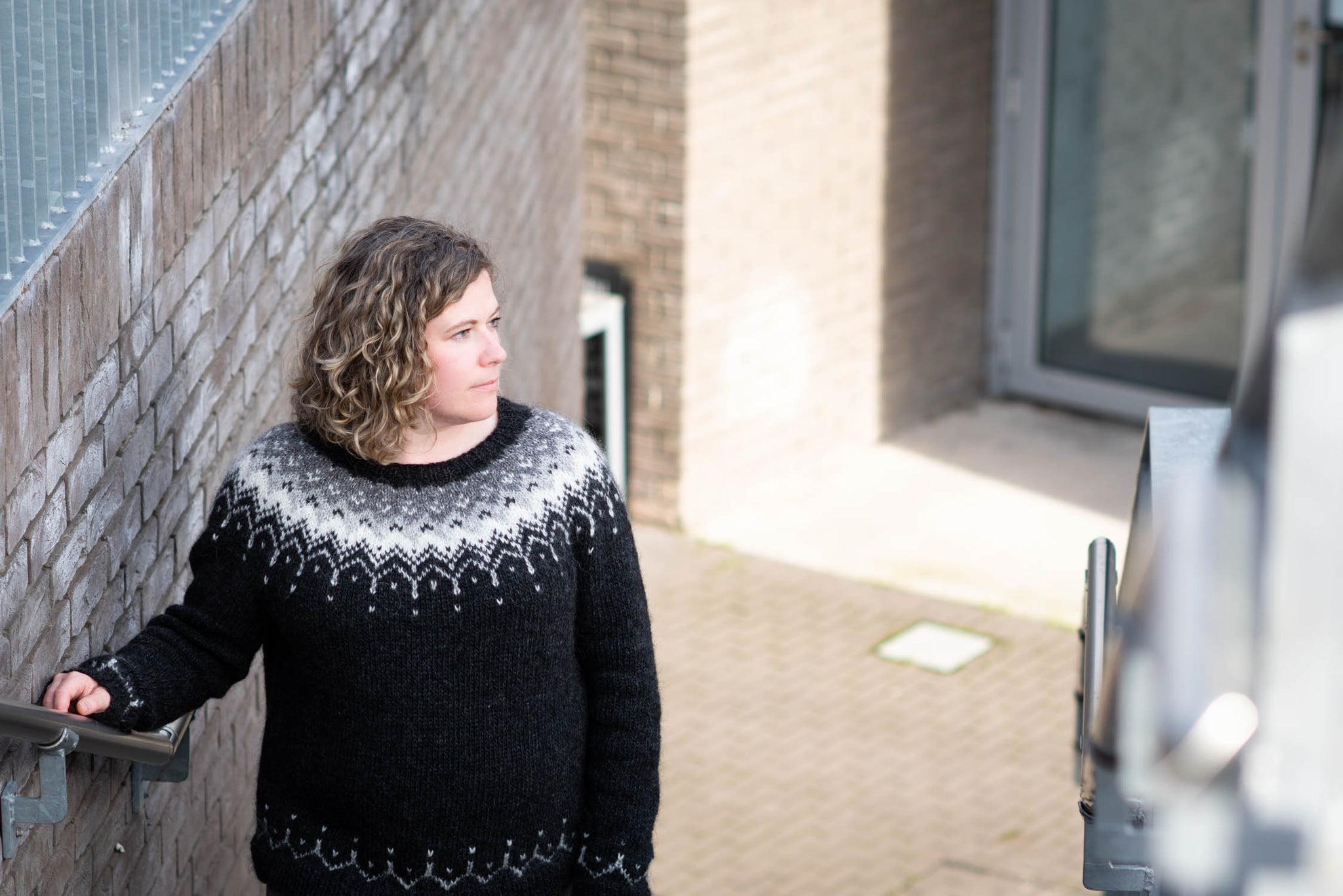 A white woman with curly hair stands in a stairway, looking to the side. She wears a black sweater with colourwork yoke and holds onto the stair rail.