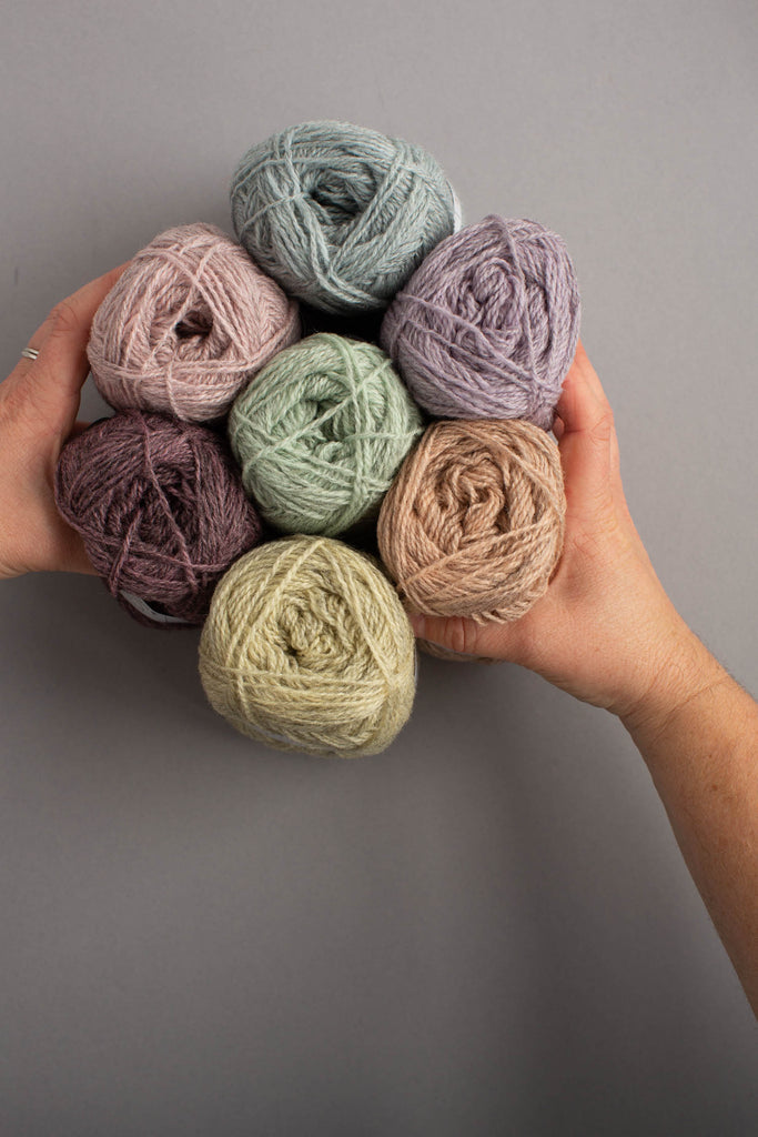 Image of balls of yarn being held in white skinned hands over a grey background