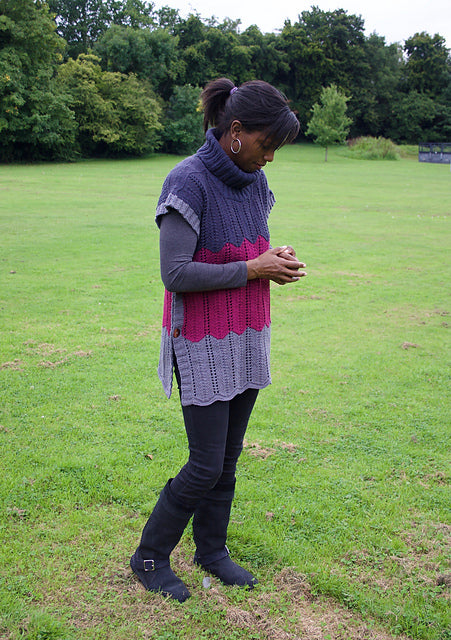 Image of a black skinned woman wearing a colour blocked lace tunic with buttons on the side and a cowl neck.