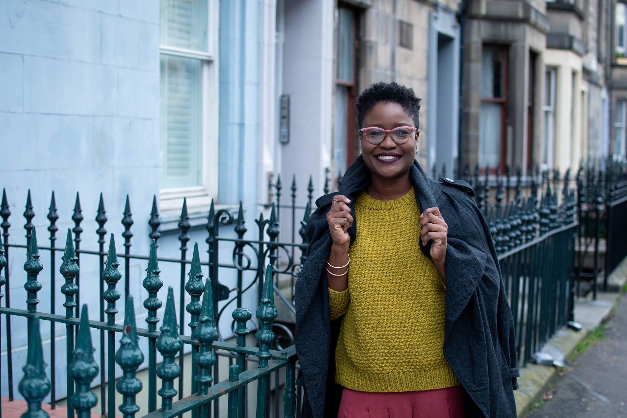A smiling black skinned woman with short hair is standing in front of some railings. She is wearing a yellow textures knitted sweater over a pink skirt. She has a raincoat thrown over her shoulders.
