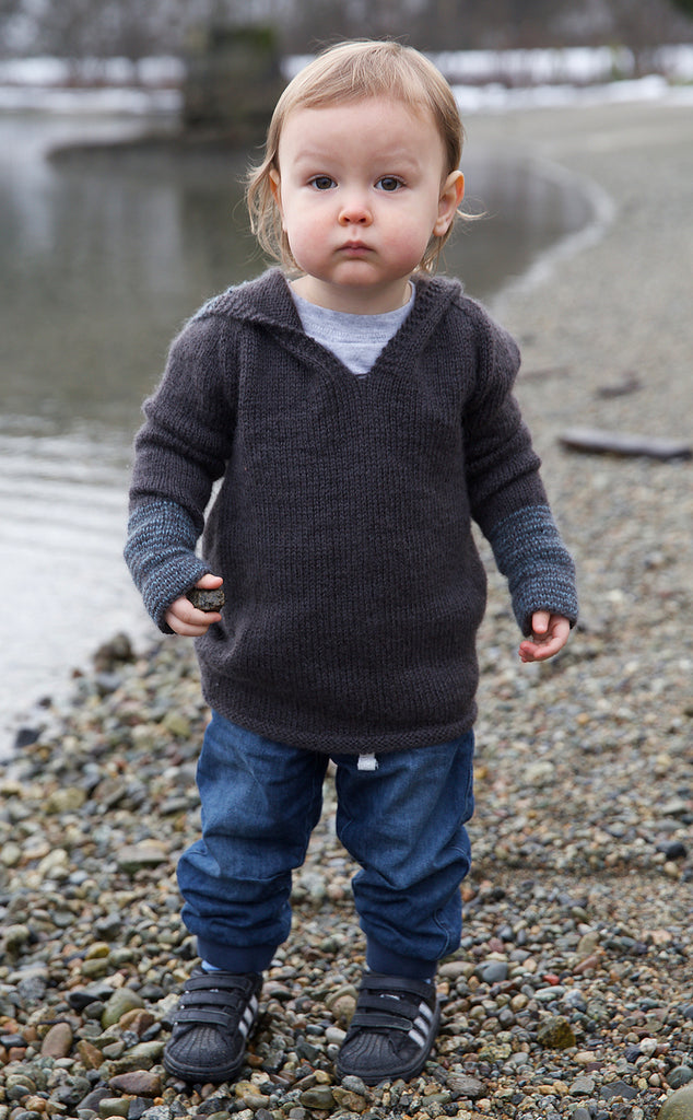 Image of a white skinned toddler in a dark hoodie with a stripe detail on the arms