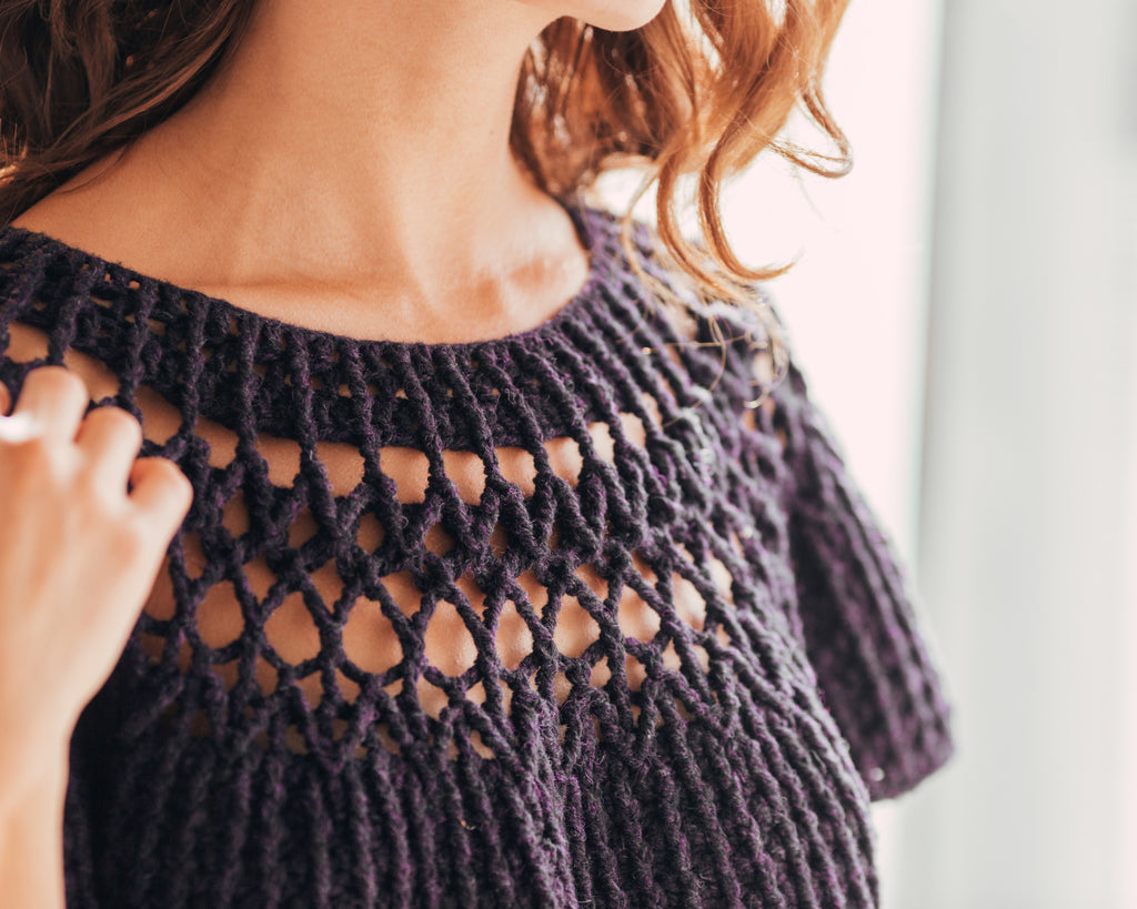 Image of a light skinned woman's shoulders. She is wearing a crocheted top with lace cut out details around the yoke.