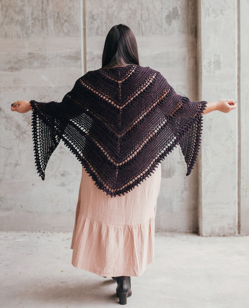 Image of a brown skinned woman with her back to the camera, wearing a crocheted triangular shawl
