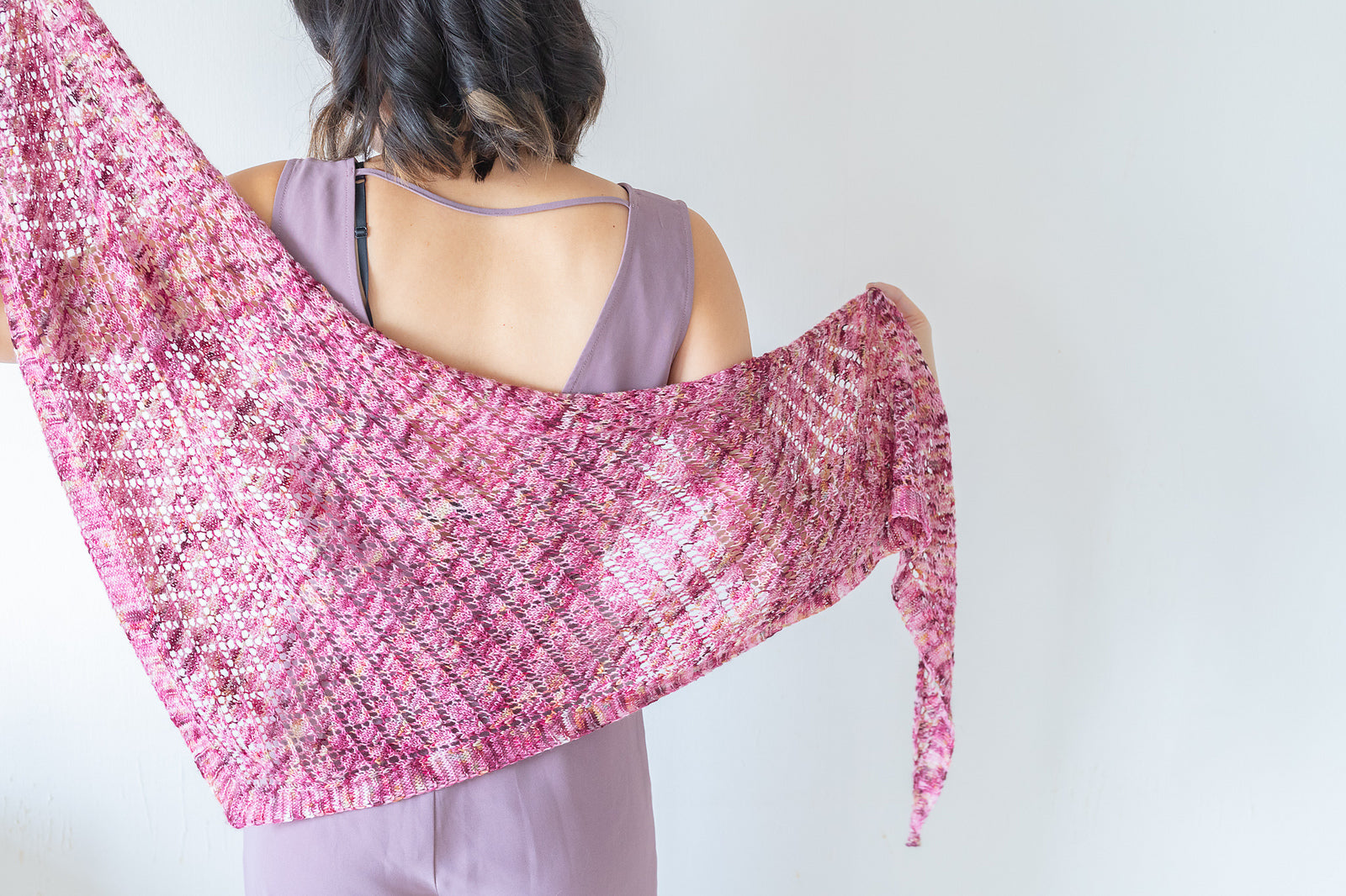 Person wearing a sleeveless purple dress with their back to the camera holding a pink, triangular lace shawl.