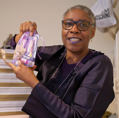 Image of a black woman with cropped grey hair holding up a gift bag