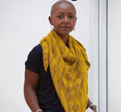 Image of a bald black woman wearing a large yellow scarf