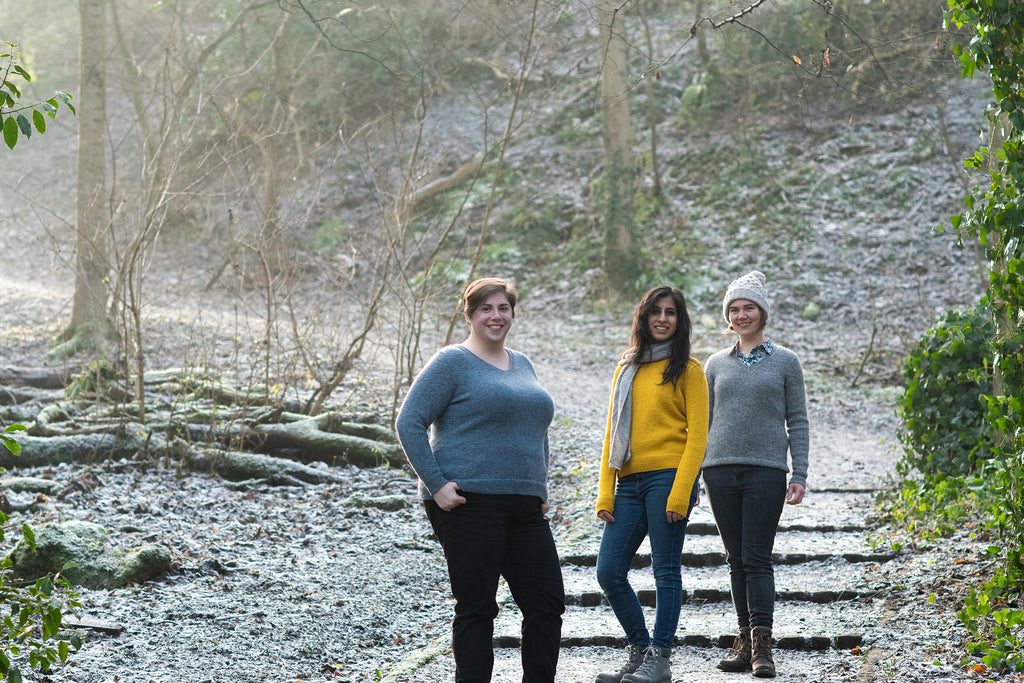 3 women posing on frost coloured stairs with trees on either side. They're all wearing dark jeans and hand knit sweaters.