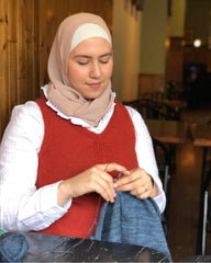 Image of an Arabic woman wearing a hijab and a red vest knitting a blue project