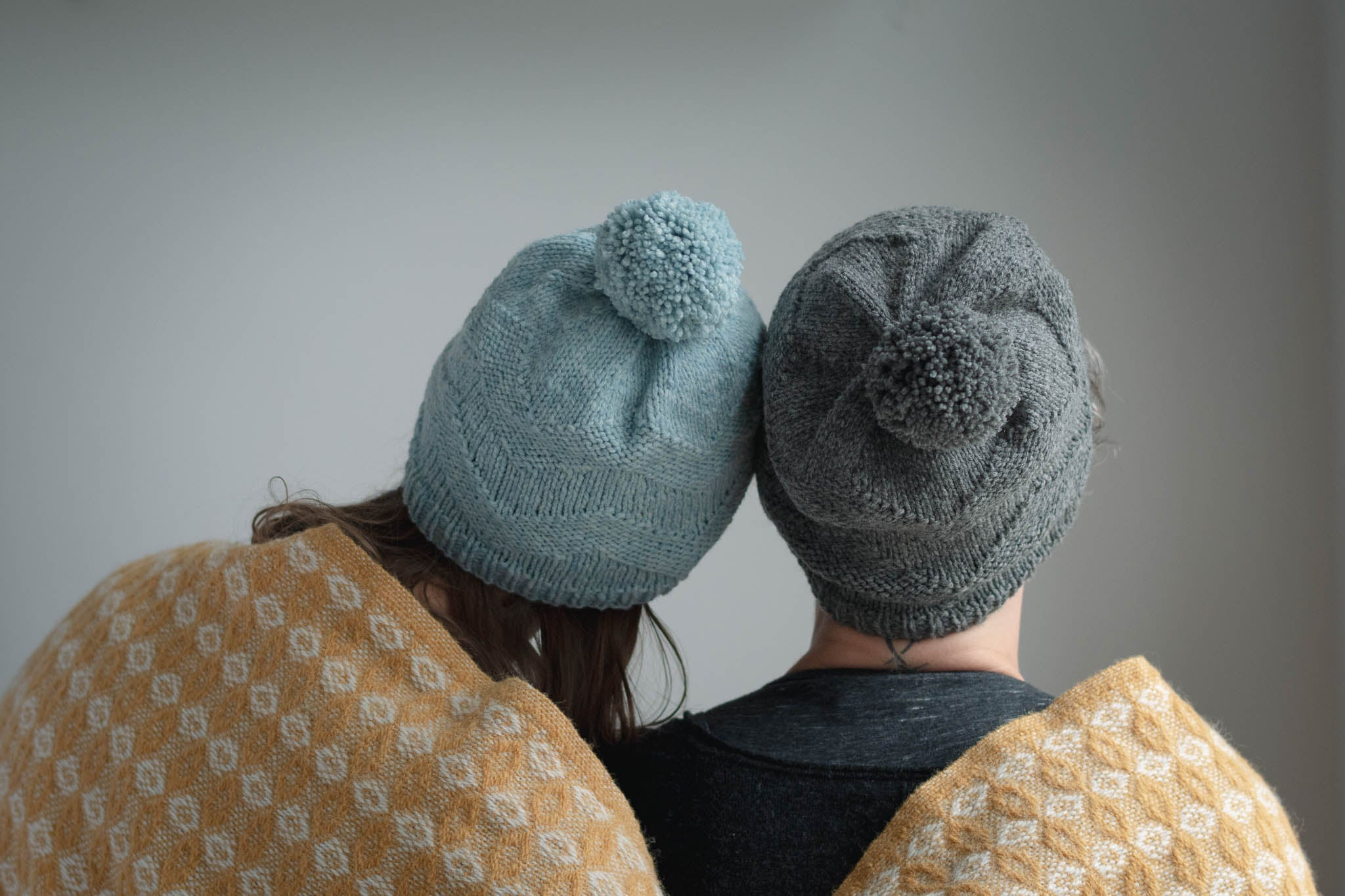 Two models face away from the camera, each wearing the same slouchy beanie hat with pom pom. They are snuggled together and wrapped in a shared yellow blanket.