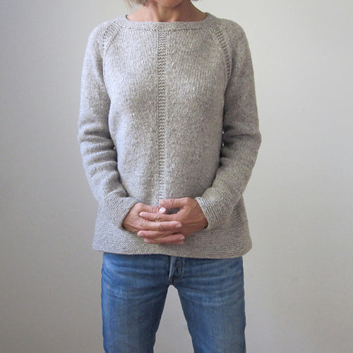 image of a torso wearing a grey jumper with a garter stitch detail in the centre over blue jeans.