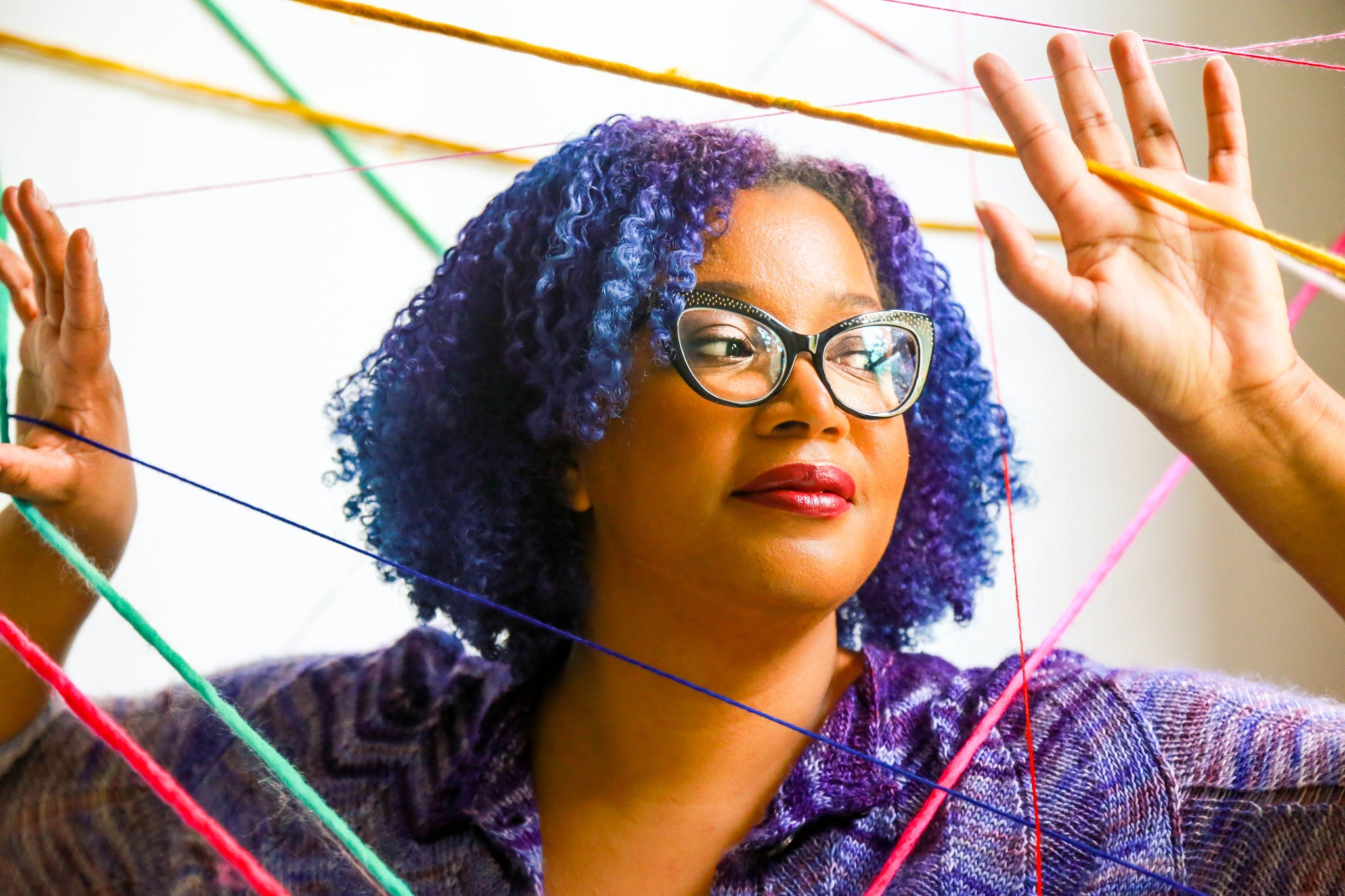 Black woman with blue and purple curls peeking through a web of colourful yarn