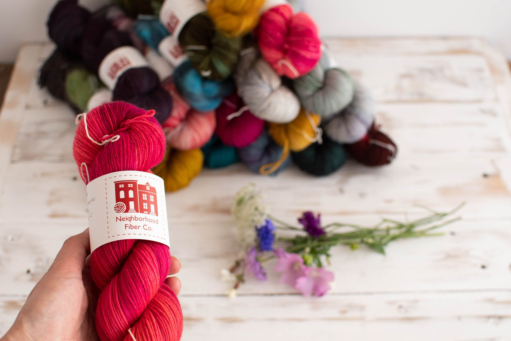pile of yarn in the background with someone holding a red and pink skein up to the camera in the foreground