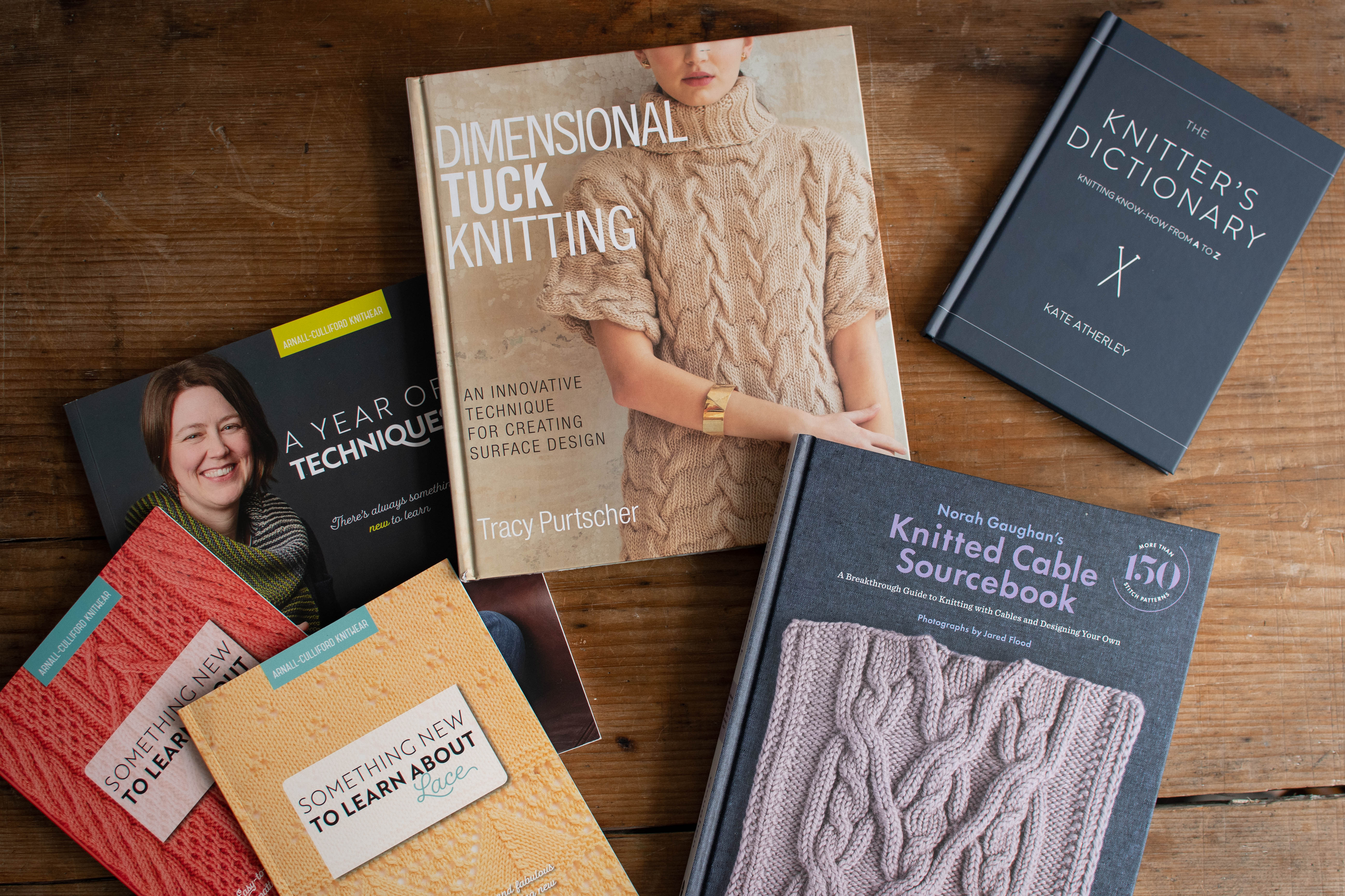 flat lay of knitting technique books on a wooden table.