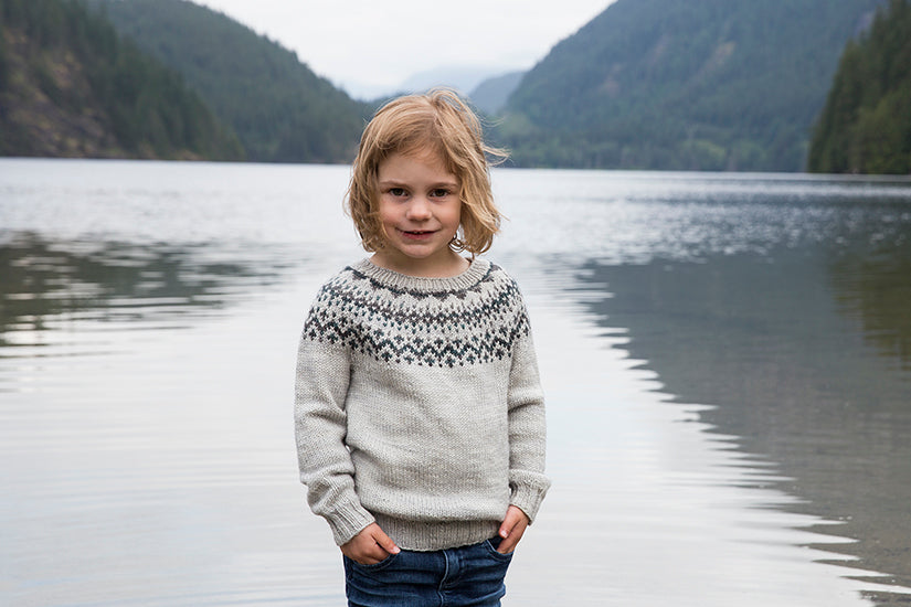 Image of a fair haired white skinned child wearing a cream sweater with a dark patterns colourwork yoke