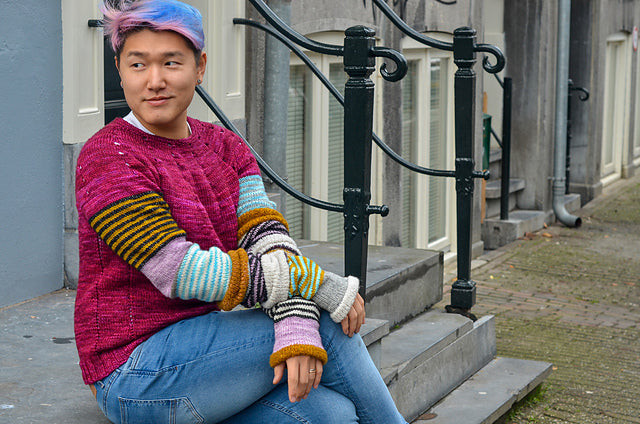 Image of an Asian man with pink and blue hair seated on steps. He is wearing a pink sweater with slouchy multi coloured sleeves.