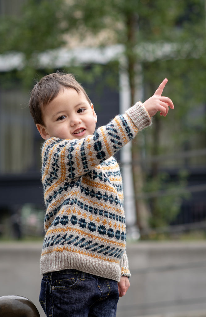 Picture of a light brown skinned child wearing a sweater with all over colourwork