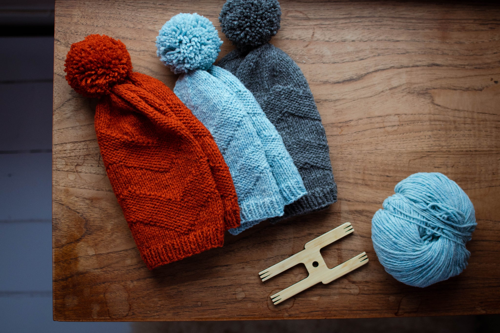 Three beanie hats lie overlapping on a wooden table. They are orange, blue and grey and folded in half. Next to them is a blue ball of yarn and a wooden pom pom tool