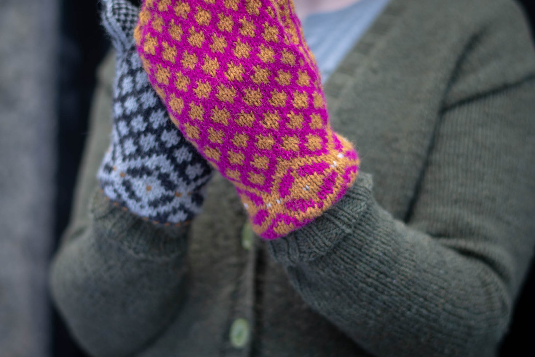 Two hands held up, clasped together. One is wearing a pink and yellow colourwork mitten, the other wears a grey mitten.